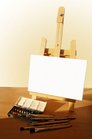 Table easel with canvas, watercolor and brushes photo