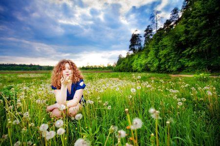 Beautiful girl blowing a dandelion photo