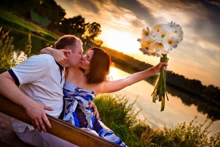 日没の若いカップルのキス