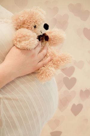 Pregnancy woman holding a teddy bear over her belly Stock Photo - 7675026