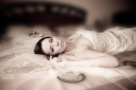 Bride portrait laying on sofa. Sepia photo