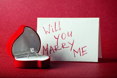 Card with ring in box on red background photo