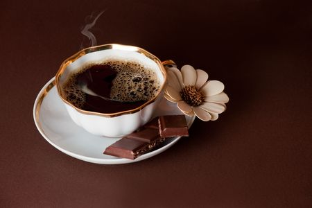 The cup of coffee with chocolate on brown background photo
