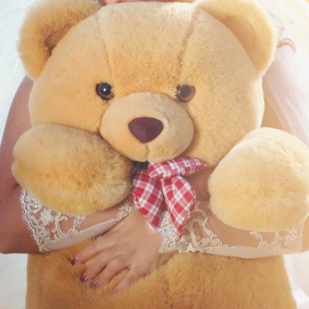 A light brown teddy bear in bride hands photo