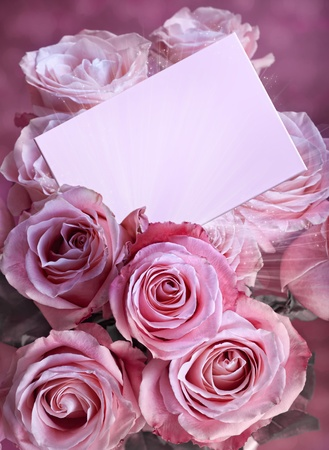A bouquet of pink roses with a greeting card photo