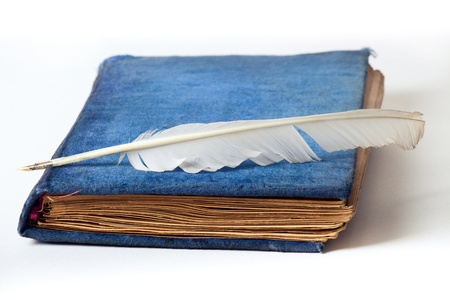 space to write: Antique blue velvet photo album with feather pen isolated on white Stock Photo