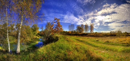 Panoramic landscape of sunny autumn field with forest river Stock Photo - 8764261