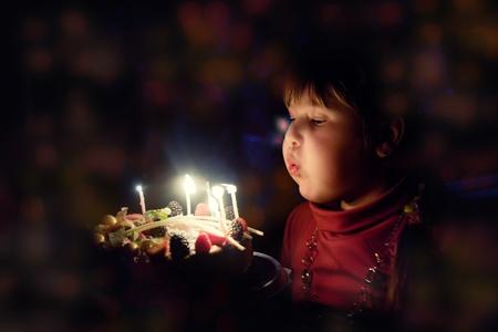 バースデー ケーキの上の蝋燭を吹く少女