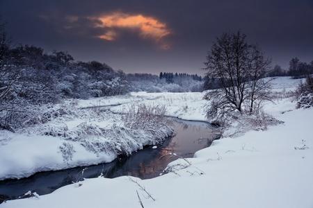 Winterlandschap met veld en bos op zonnige avond