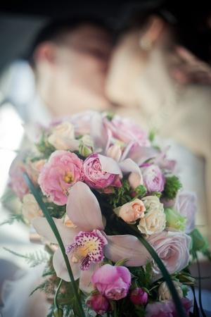 Zoenen jonggehuwden met bruidsboeket Stockfoto