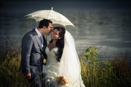 Newlyweds posing near autumn lake photo