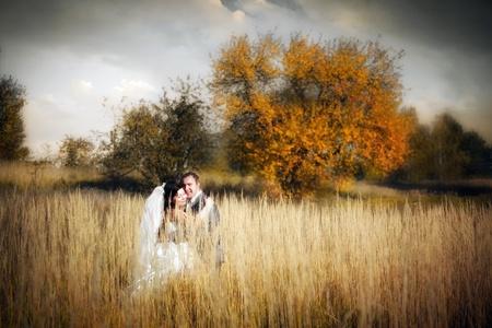 秋のフィールドでの新婚夫婦のキス