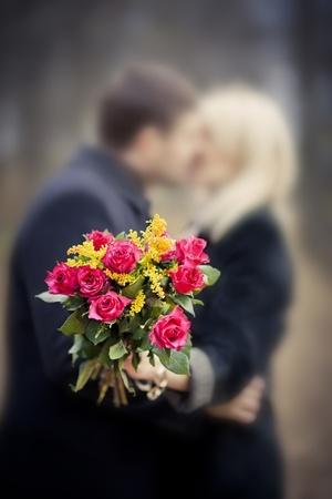 Gelukkig jong koppel met rozen boeket op een datum