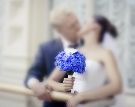 Kissing newlyweds with the Hydrangea bouquet. Soft focus on bouquet photo