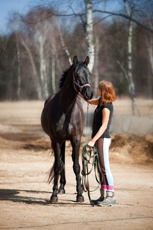 Young woman standing near horse Stock Photo - 11354219
