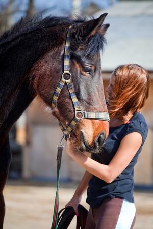 Portret van lachende jonge vrouw met paard