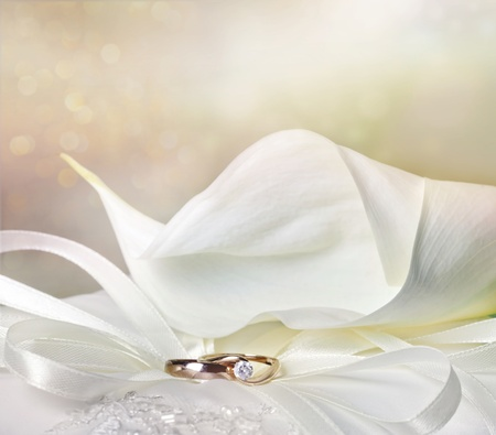 Wedding background with calla lilies and golden rings photo
