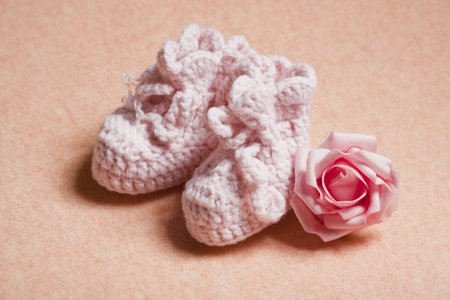 Pink baby shoes on peach background Stock Photo - 12117557