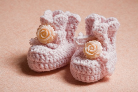 Pink baby shoes on peach background photo