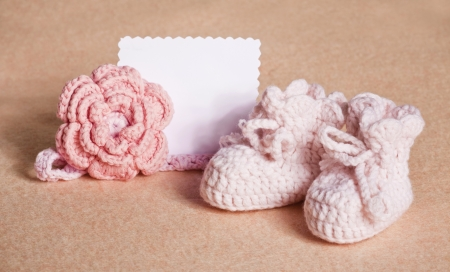 桃の背景にピンクのベビー シューズ 写真素材