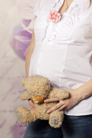 Pregnant woman holding a teddy bear over her belly Stock Photo - 12117589