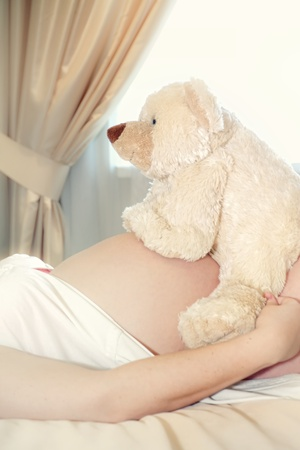 Pregnant woman holding a teddy bear over her belly photo