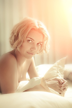 Young sexy beautiful woman in soft morning light photo