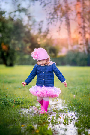 Cute little girl in rain boots running on puddles Stock Photo
