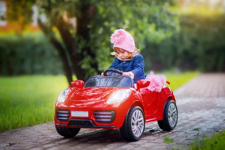 Modieus Meisje met speelgoed rode auto cabriolet Stockfoto - 80598705