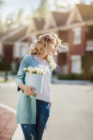 seller: Beautiful woman with paper box of flowers outdoor portrait on town  street