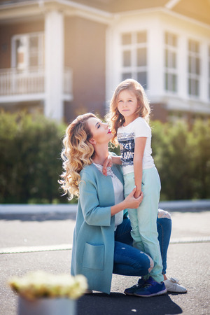 Mother and daughter walking on street at sunny summer day