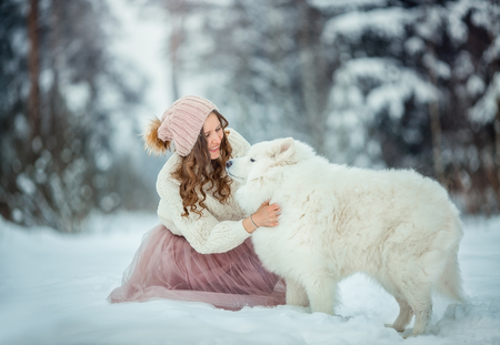 Beautiful woman with dog samoyed in winter forest Stock Photo