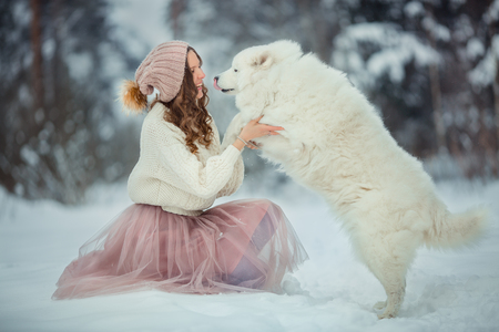Beautiful woman with dog samoyed in winter forest Standard-Bild