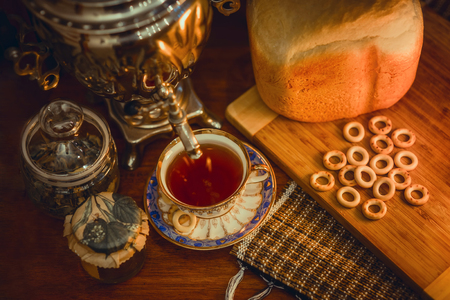 Russian traditional samovar with hot bread and ceramic cup of tea