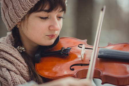 Teenage girl portrait with violin in winter park