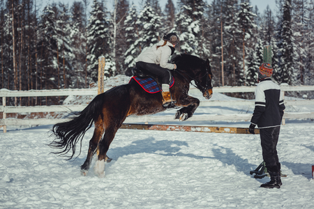 Winter teenage girl jump horse ride jumping