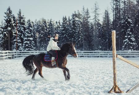 Winter teenage girl jump horse ride jumping Stock Photo - 96826008
