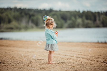 Little girl have fun on the coast of the lake Stok Fotoğraf