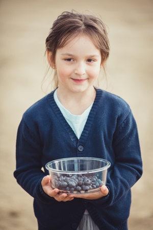 The girl eating blueberries from a glass bowl outdoor