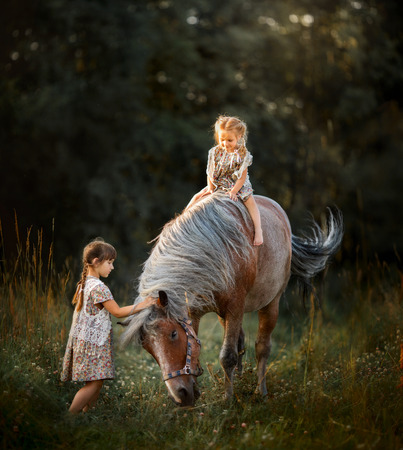 Little sisters with horse at summer cloudy evening