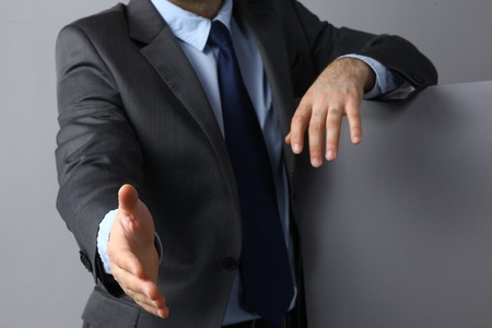 headman: Man wearing a suit offering to shake hands .