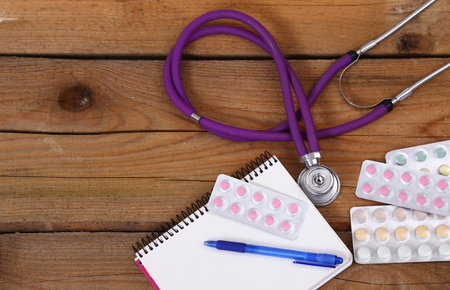Stethoscope and tablets isolated on wooden background