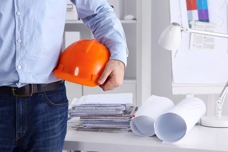 architect: Man architect wearing suit holding helmet, standing in office.
