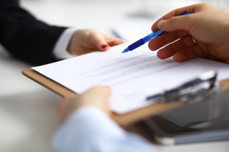 subpoena: Close up of an executive hands holding a pen and indicating where to sign a contract at office.
