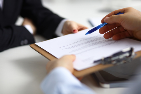 Close up of an executive hands holding a pen and indicating where to sign a contract at office.