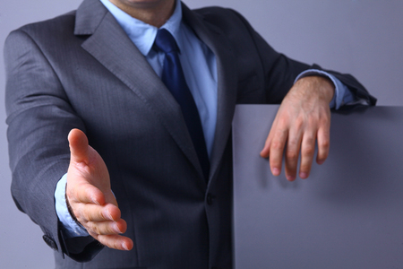Man wearing a suit offering to shake hands Stock Photo