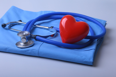 Doctor coat with medical stethoscope and red heart on the desk 写真素材