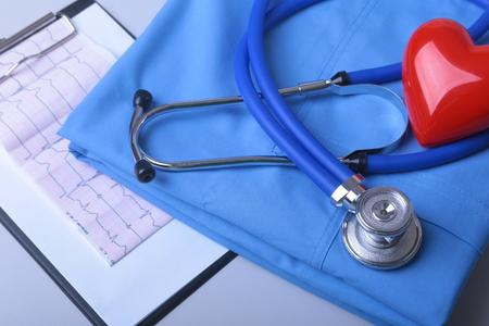 Kardiogramm mit medizinischem Stethoskop und rotem Herzen mit Arztmantel auf Tisch