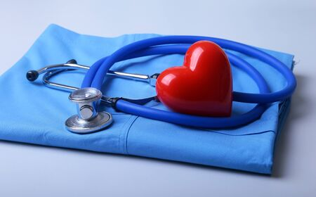 Doctor coat with medical stethoscope and red heart on the desk 版權商用圖片