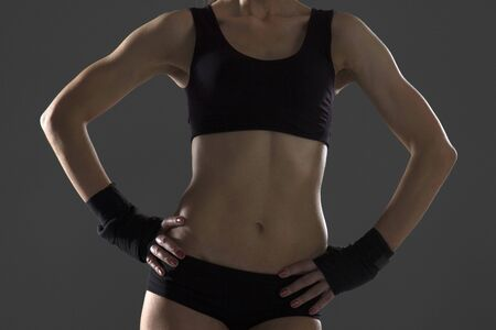 Happy young woman in sports clothing smiling. Muscular fitness model on black background looking away at copy space